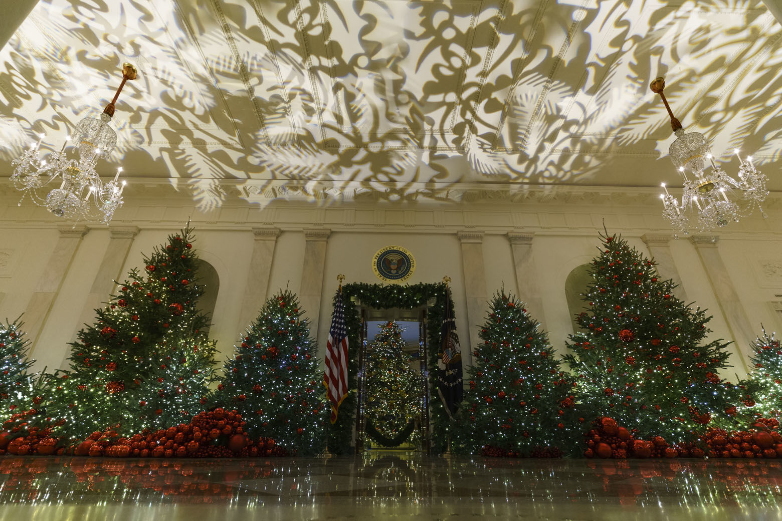 "Grand Foyer and Cross Hall leading into the Blue Room and the official White House Christmas tree are seen during the 2018 Christmas Press Preview at the White House in Washington, Monday, Nov. 26, 2018. Christmas has arrived at the White House. First lady Melania Trump unveiled the 2018 White House holiday decor on Monday. She designed the decor, which features a theme of ""American Treasures."" (AP Photo/Carolyn Kaster)"