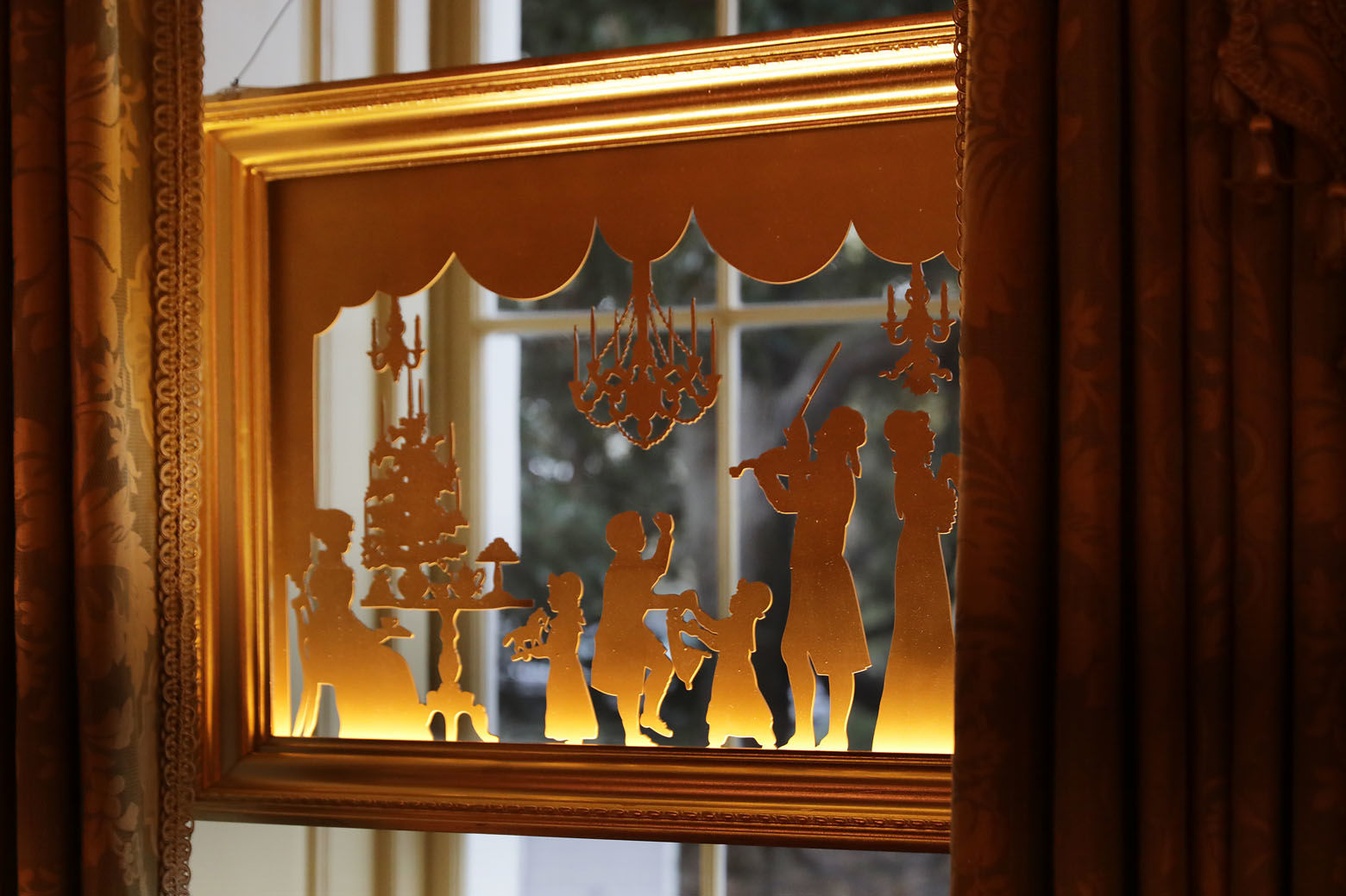 WASHINGTON, DC - NOVEMBER 26: A window silhouette of U.S. President Thomas Jefferson playing the violin for his family in 1805 hangs in a window of the Vermeil Room which is decorated for the holidays at the White House November 26, 2018 in Washington, DC. The 2018 theme of the White House holiday decorations is 'American Treasures,' and features patriotic displays highlighting the country's 'unique heritage.' The White House expects to host 100 open houses and more than 30,000 guests who will tour the topiary trees, architectural models of major U.S. cities, the Gold Star family tree and national monuments in gingerbread. (Photo by Chip Somodevilla/Getty Images)