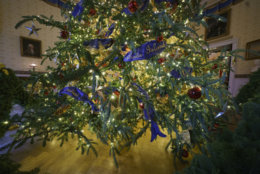 "The base of the official White House Christmas tree is seen in the Blue Room during the 2018 Christmas Press Preview at the White House in Washington, Monday, Nov. 26, 2018. The tree measures 18 feet tall and is dressed in over 500 feet of blue velvet ribbon embroidered in gold with each State and territory. Christmas has arrived at the White House. First lady Melania Trump unveiled the 2018 White House holiday decor on Monday. She designed the decor, which features a theme of ""American Treasures."" (AP Photo/Carolyn Kaster)"