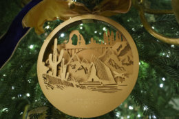 An ornament with images of the Southwest and the Intermountain West hangs on a tree in the East Room to highlight the diversity and ingenuity of American architecture and design during the 2018 Christmas preview at the White House in Washington, Monday, Nov. 26, 2018.  (AP Photo/Carolyn Kaster)