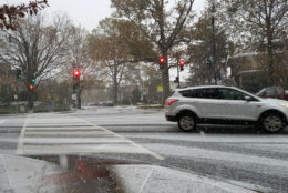 Cars make their way through Northwest D.C. as snow falls Thursday. (WTOP/Will Vitka)