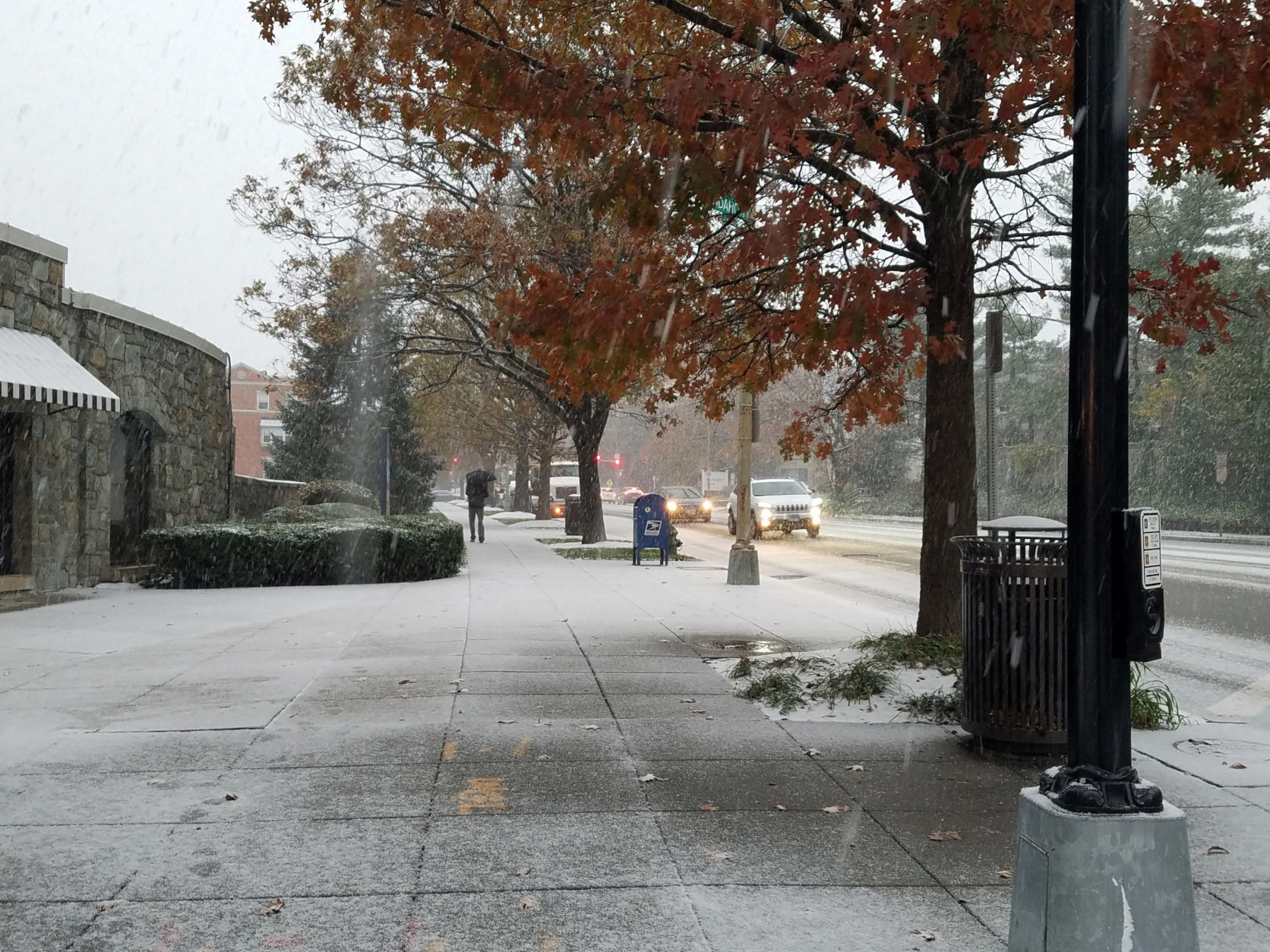 A man makes his way down Wisconsin Ave. in Northwest D.C. as snow falls around him. (WTOP/Will Vitka)