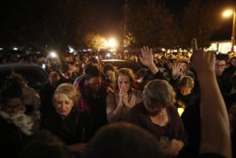 People gather outside the Rivalry Roasters coffee shop for a vigil for Sean Adler Thursday, Nov. 8, 2018, in Simi Valley, Calif. Adler was killed in Wednesday night's shooting at the Borderline Bar and Grill in Thousand Oaks, Calif. (AP Photo/Jae C. Hong)