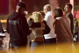 """People comfort each other as they stand near the scene Thursday, Nov. 8, 2018, in Thousand Oaks, Calif., where a gunman opened fire Wednesday inside a country dance bar crowded with hundreds of people on """"college night,"""" wounding multiple people including a deputy who rushed to the scene.  (AP Photo/Mark J. Terrill)"""
