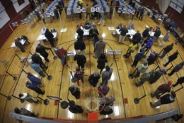 Voters wait in line in the gymnasium at Brunswick Junior High School to receive their ballots for the mid-term election, Tuesday, Nov. 6, 2018, in Brunswick, Maine. (AP Photo/Robert F. Bukaty)