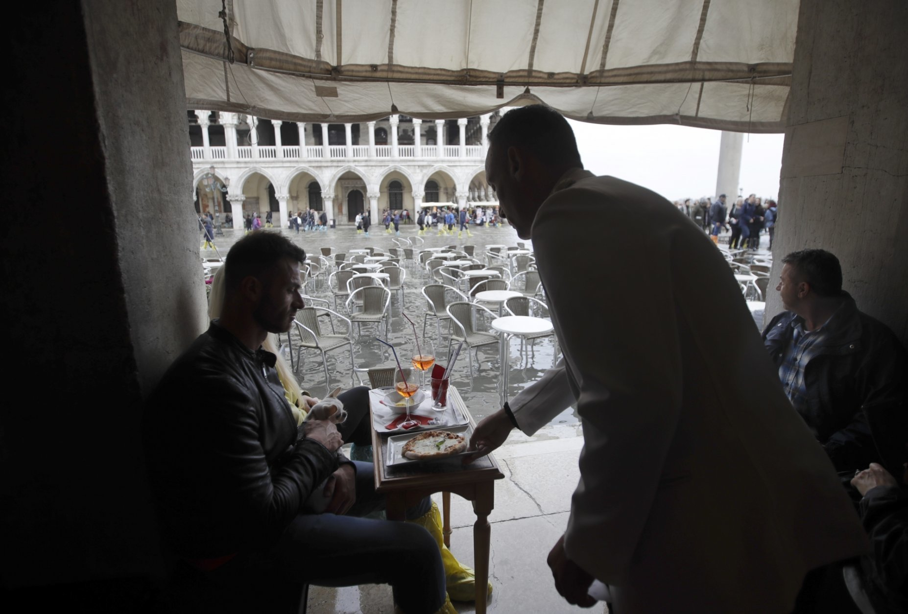 A client is served pizza in a cafe' in flooded St. Mark's Square in Venice, Italy, Thursday, Nov. 1, 2018 as rainstorms and strong winds have been battering the country. Two people were killed when a falling tree crushed their car in the mountainous countryside in northwestern Italy, as rainstorms and strong winds continued to pummel much of the country. (AP Photo/Luca Bruno)