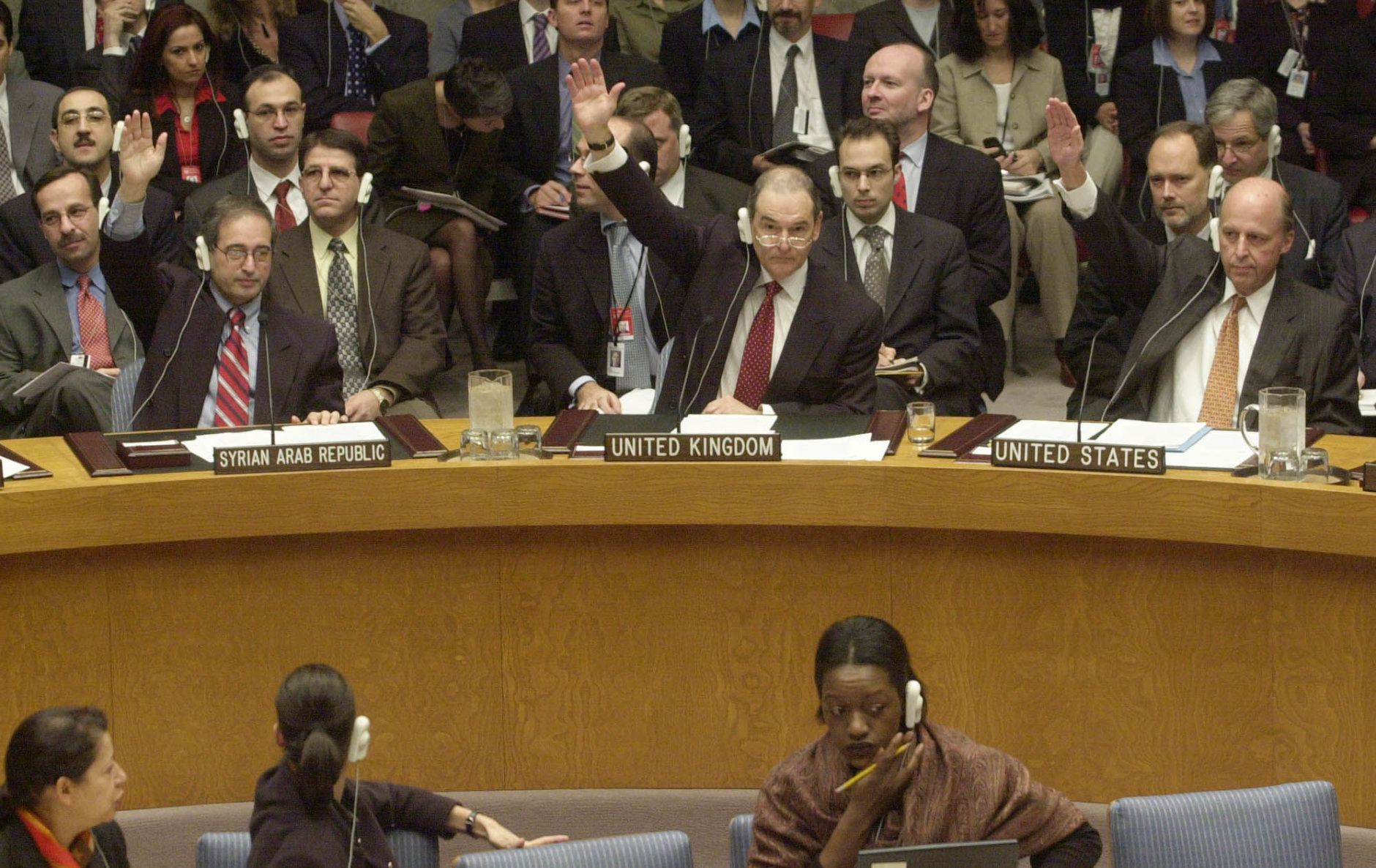 """Left to right, Syria's deputy U.N. Ambassador Fayssal Mekdad, Britain's Ambassador Jeremy Greenstock and U.S. Amabassador John Negroponte vote on an Iraq resolution in the U.N. Security Council chambers Friday, Nov. 8, 2002.  The Security Council unanimously approved a tough new Iraq resolution Friday, aimed at forcing Saddam Hussein to disarm or face """"serious consequences'' that would almost certainly mean war. (AP Photo/Bebeto Matthews)"""
