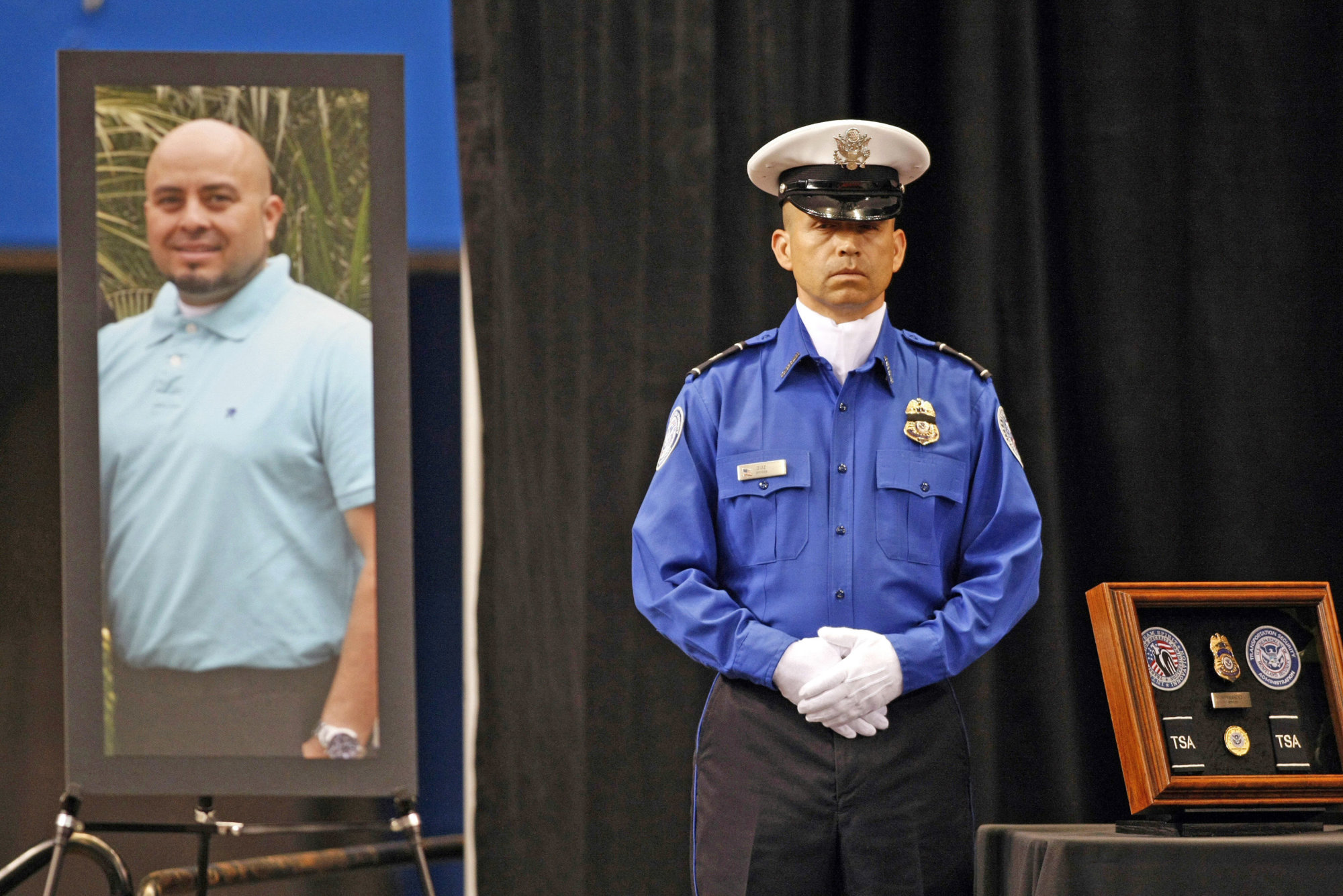 FILE - In this Nov. 12, 2013 file photo, a Transportation Security Administration officer stands in front of a portrait of slain TSA officer Gerardo Hernandez during his public memorial at the Los Angeles Sports Arena. Paul Ciancia, the gunman who killed the federal security officer at Los Angeles International Airport and wounded three other people during a 2013 rampage, faces sentencing for murder and other crimes. Ciancia is expected to be sentenced Monday, Nov. 7, 2016, to life in prison for shootings that terrorized passengers and employees at the nation's second-busiest airport and disrupted air travel nationwide. (Al Seib/Los Angeles Times via AP, Pool, File)
