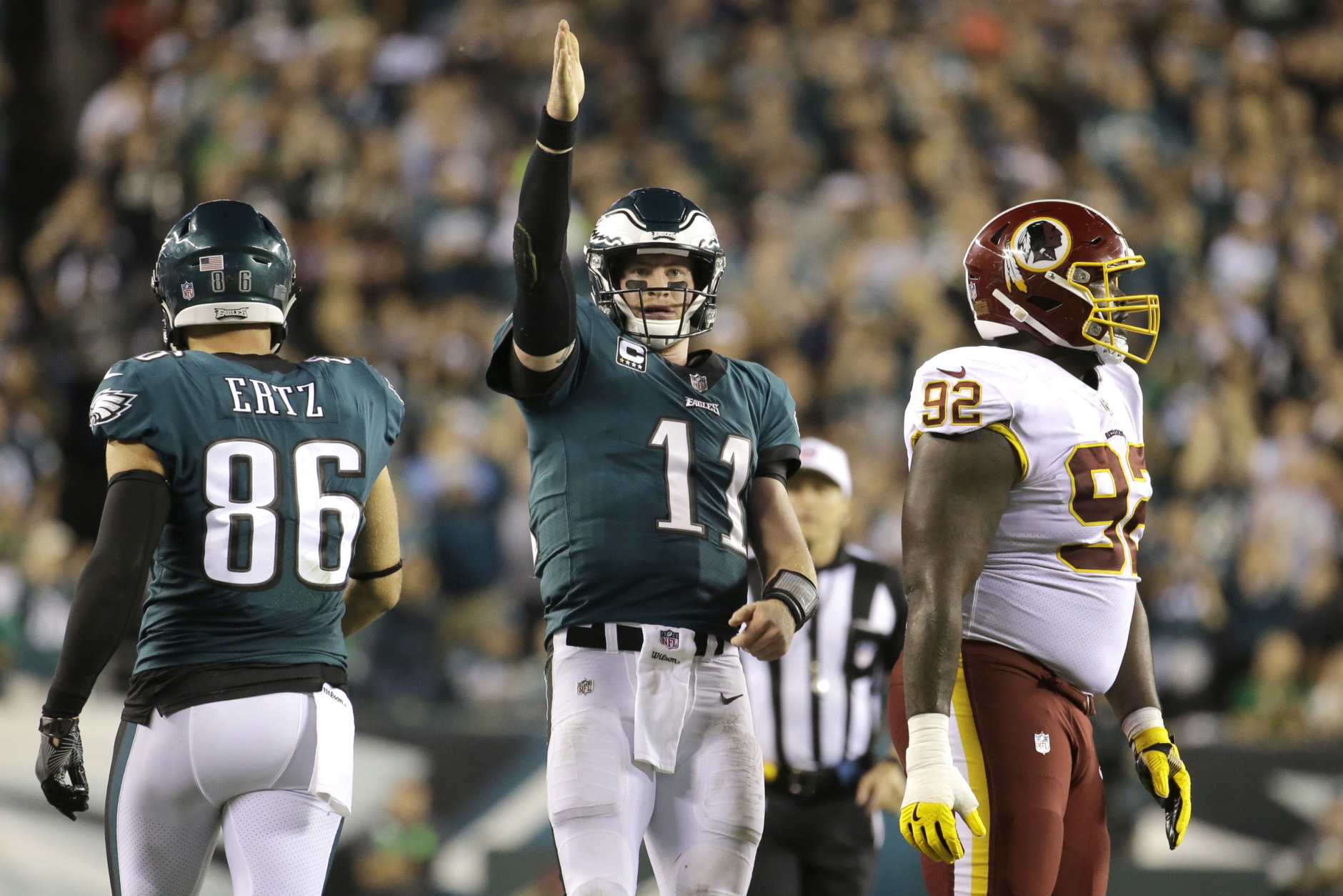 FILE - In this Monday, Oct. 23, 2017, file photo, Philadelphia Eagles quarterback Carson Wentz (11) gestures after scrambling for yardage against the Washington Redskins during the second half of an NFL football game in Philadelphia. Wentz and the Philadelphia Eagles are the talk of the NFL following a surprising 6-1 start and impressive victories in consecutive prime-time games.  (AP Photo/Michael Perez, File)