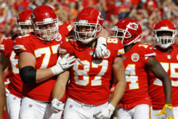 Kansas City Chiefs tight end Travis Kelce (87) celebrates a touchdown in front of offensive lineman Andrew Wylie (77) and wide receiver Sammy Watkins (14) during the first half of an NFL football game against the Denver Broncos in Kansas City, Mo., Sunday, Oct. 28, 2018. (AP Photo/Charlie Riedel)