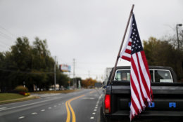 An American flag hangs on the back of a pickup truck on election day as a motorist drives through Woodstock, Ga., Tuesday, Nov. 6, 2018. Across the country, voters headed to the polls Tuesday in one of the most high-profile midterm elections in years. (AP Photo/David Goldman)