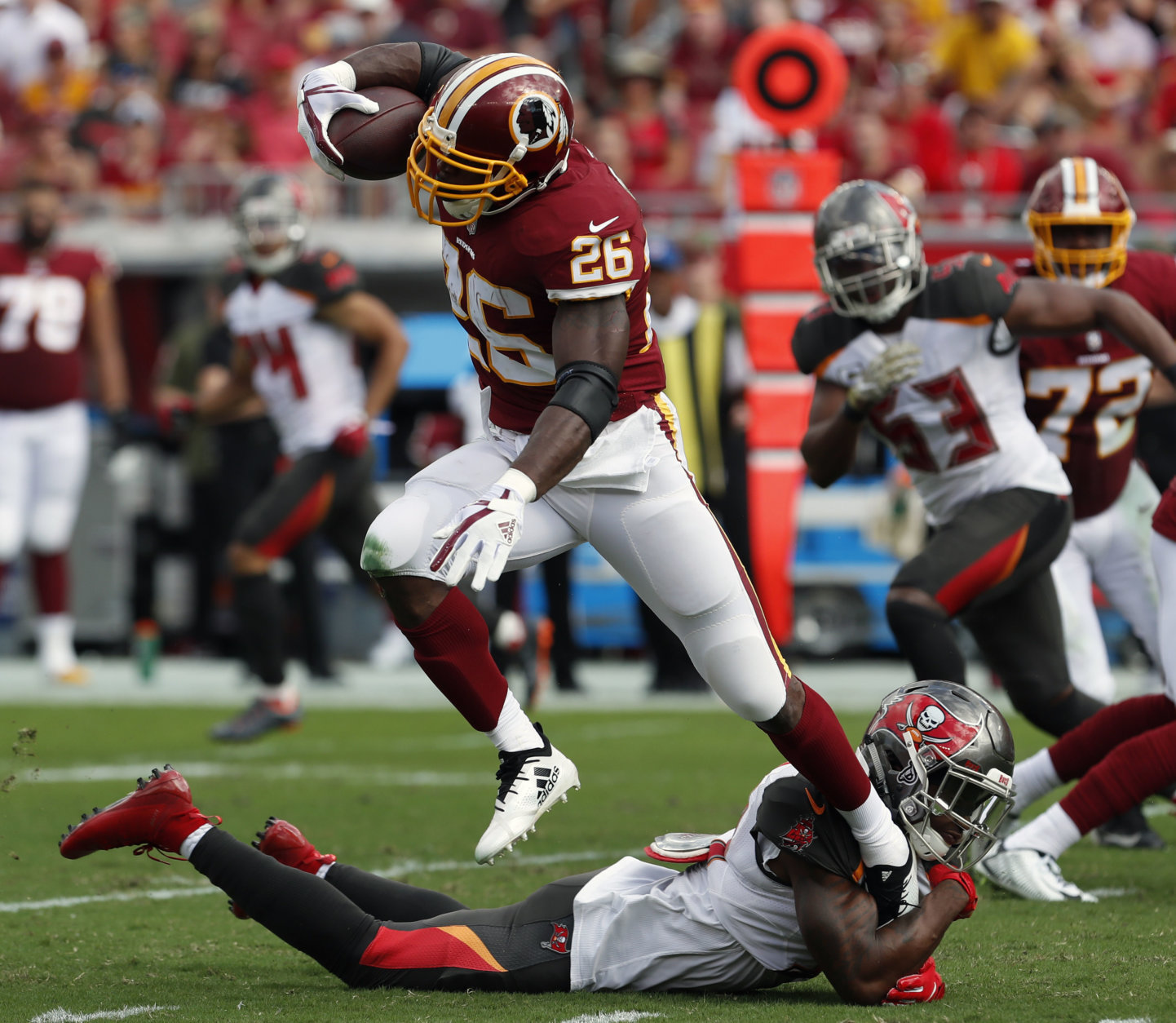 Washington Redskins running back Adrian Peterson (26) eludes a tackle by Tampa Bay Buccaneers free safety Jordan Whitehead (31) during the first half of an NFL football game Sunday, Nov. 11, 2018, in Tampa, Fla. (AP Photo/Mark LoMoglio)