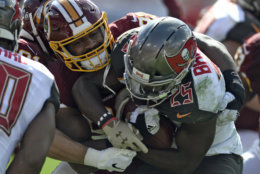 Washington Redskins defensive end Jonathan Allen (93) stops Tampa Bay Buccaneers running back Peyton Barber (25) on a run during the first half of an NFL football game Sunday, Nov. 11, 2018, in Tampa, Fla. (AP Photo/Jason Behnken)