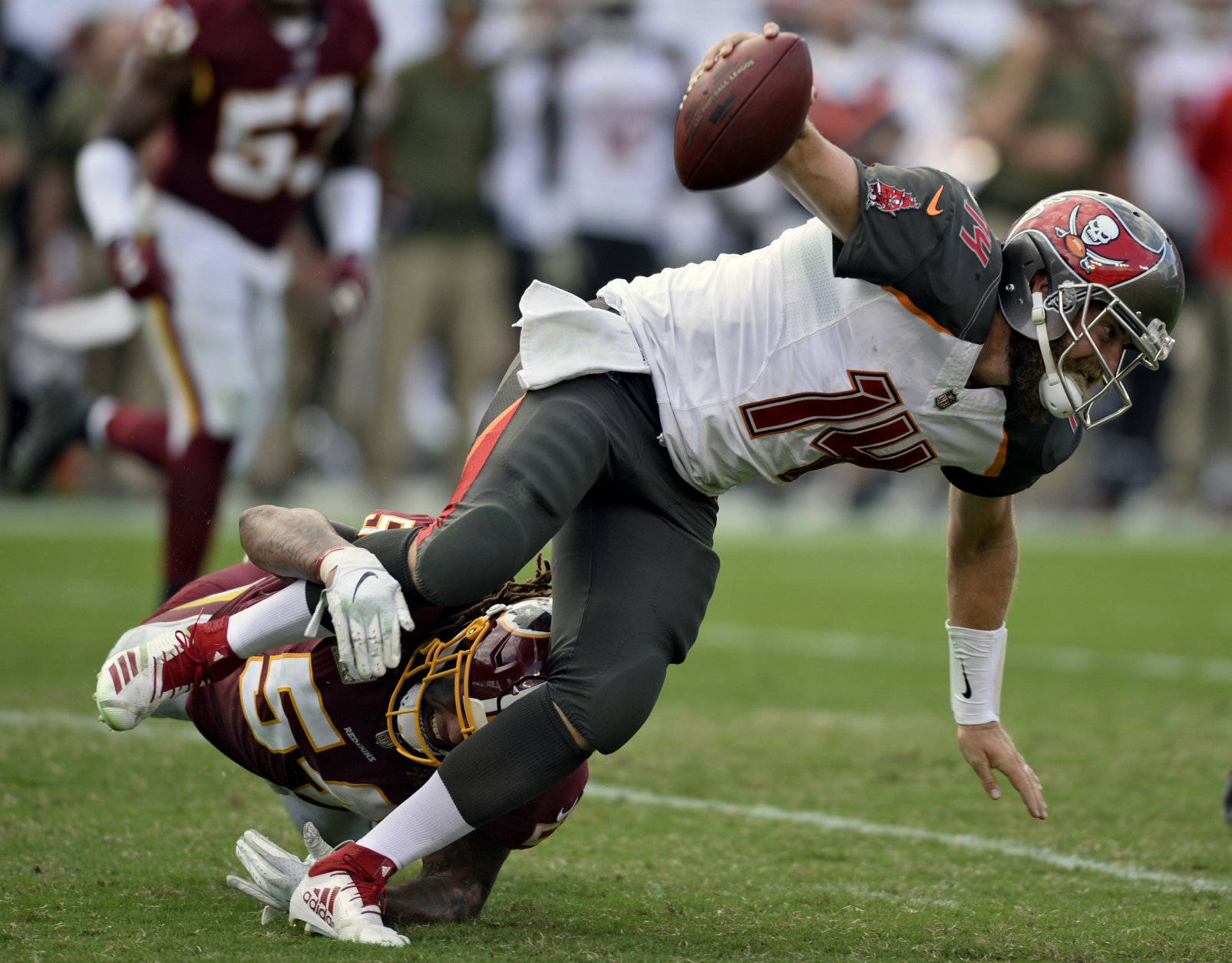 Tampa Bay Buccaneers quarterback Ryan Fitzpatrick (14) is tripped by Washington Redskins inside linebacker Mason Foster (54) during the second half of an NFL football game Sunday, Nov. 11, 2018, in Tampa, Fla. (AP Photo/Jason Behnken)