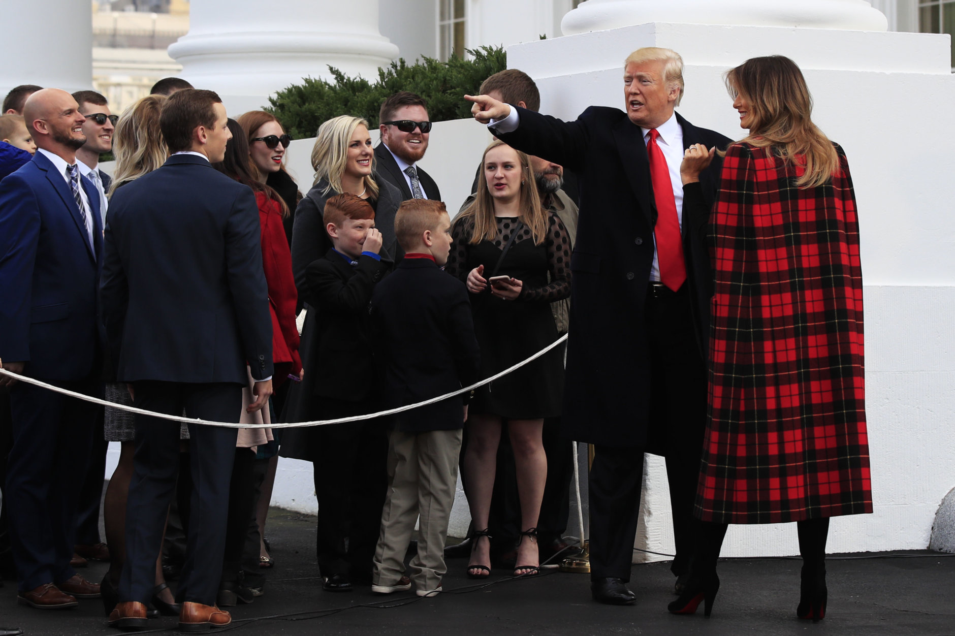 President Donald Trump and first lady Melania Trump wave to invited guests during a ceremony to receive the White House Christmas Tree, presented by tree grower Larry Smith and the Smith family at the North Portico of the White House, in Washington, Monday, Nov. 19, 2018. The North Carolina-grown 19 1/2-foot-tall Fraser Fir will be displayed in the Blue Room of the White House. (AP Photo/Manuel Balce Ceneta)