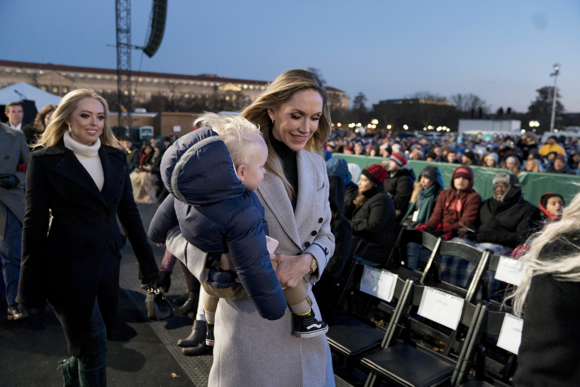Lara Trump, the wife of Eric Trump carries her son Eric, as she and Tiffany Trump, the daughter of President Donald Trump, left, arrives for the National Christmas Tree lighting ceremony at the Ellipse near the White House in Washington, Wednesday, Nov. 28, 2018. (AP Photo/Andrew Harnik)