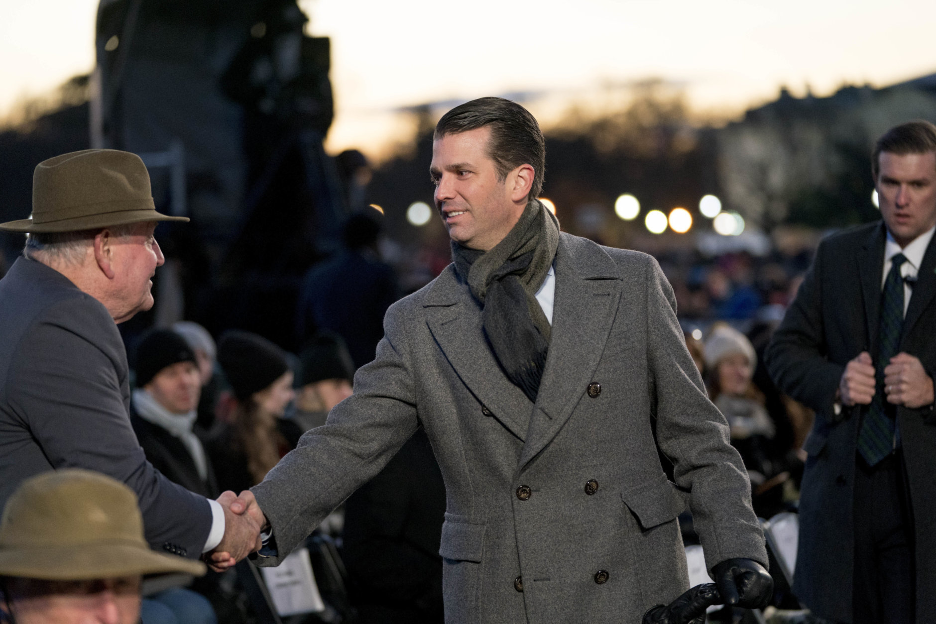 Donald Trump Jr. shakes hands with Agriculture Secretary Sonny Perdue, left, ahead of President Donald Trump and first lady Melania Trump for the National Christmas Tree lighting ceremony at the Ellipse near the White House in Washington, Wednesday, Nov. 28, 2018. (AP Photo/Andrew Harnik)