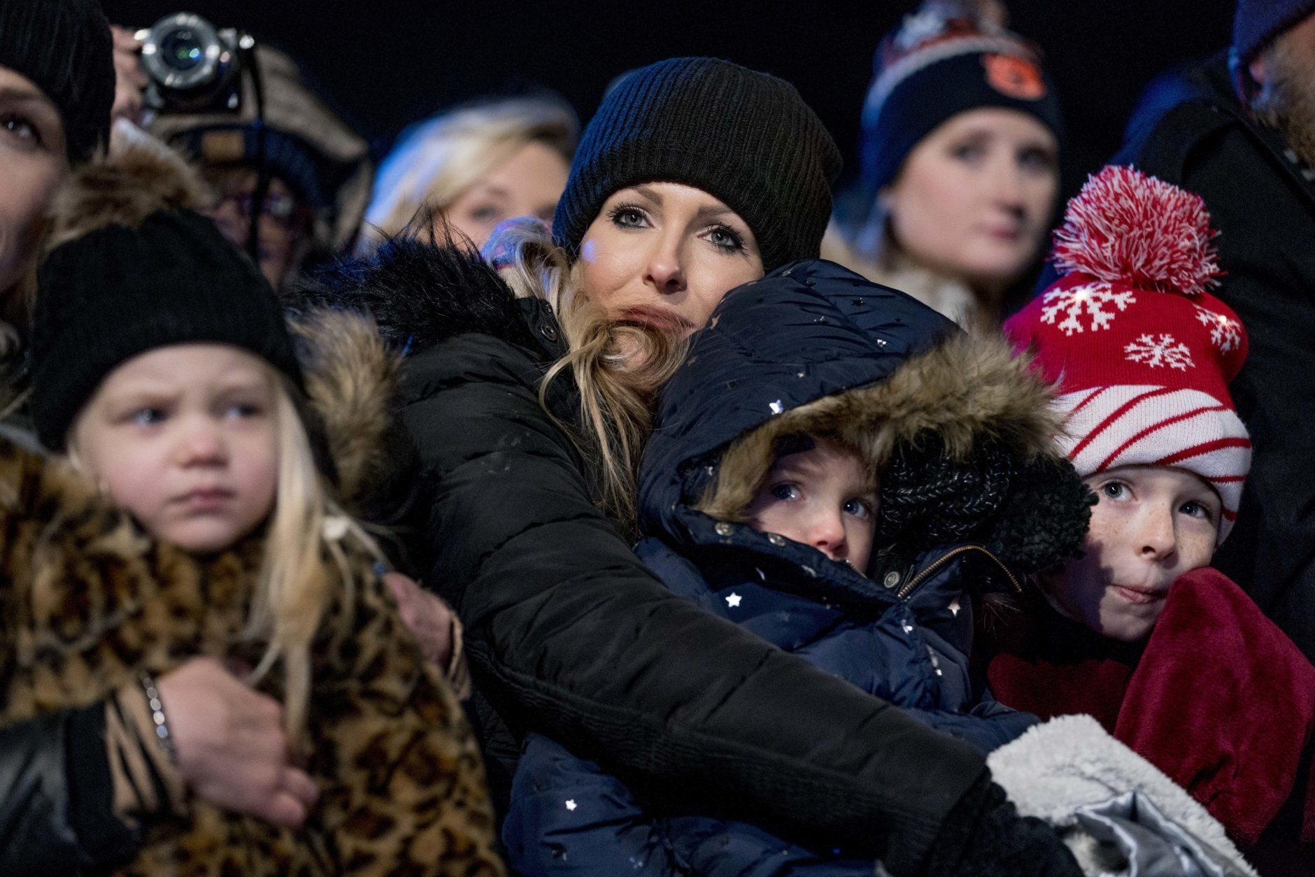 A woman and children in the front row huddle together to stay warm during the National Christmas Tree lighting ceremony at the Ellipse near the White House in Washington, Wednesday, Nov. 28, 2018. (AP Photo/Andrew Harnik)