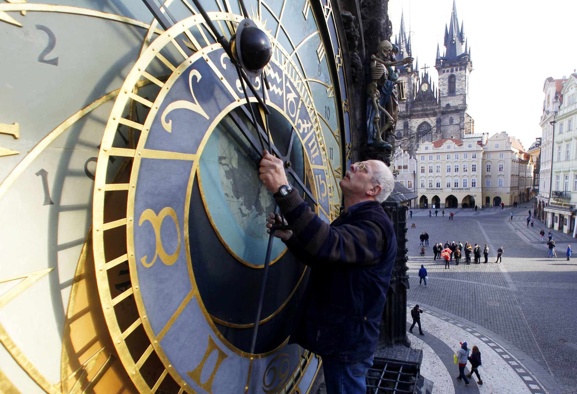 FILE - This Feb. 24, 2012 file photo shows Petr Skala performing his weekly maintenance of the famous Astronomical clock at the Old Town Square in Prague, Czech Republic. The clock was first installed in 1410, making it the third-oldest astronomical clock in the world and it is supposed to be  the oldest one still working. (AP Photo/Petr David Josek)