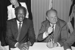 New York Mayor Edward Koch, right, gives the thumbs-up sign as he sits with Washington Mayor Marion Barry, Monday, July 1, 1985 at the National Press Club in Washington. The men were at the Press Club for a gala salute to the National Press Club/Washington press Club merger party. (AP Photo/Ken Heinen)