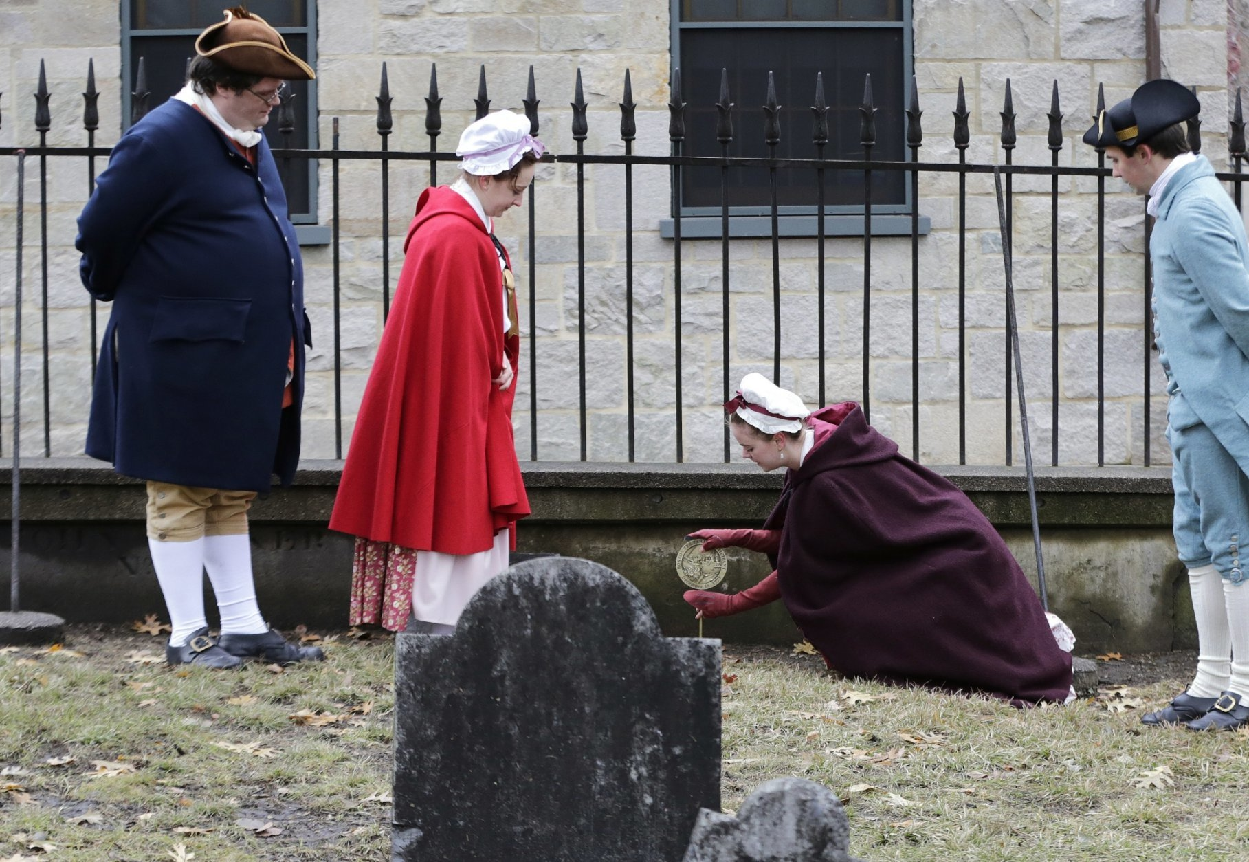 Actor-interpreters from the Boston Tea Party Ships and Museum, from left, Tim Lawton, Jillian Couillard, Sierra Grabowska and Stephen Chueka place commemorative markers, Tuesday, Nov. 27, 2018, at Central Burying Ground on Boston Common at the graves of participants in the Dec. 16, 1773 protest known as the Boston Tea Party. This year is the 245th anniversary of the protest during which colonists protesting taxation without representation threw British tea into Boston Harbor, considered a pivotal event that led to the American Revolution. (AP Photo/Elise Amendola)