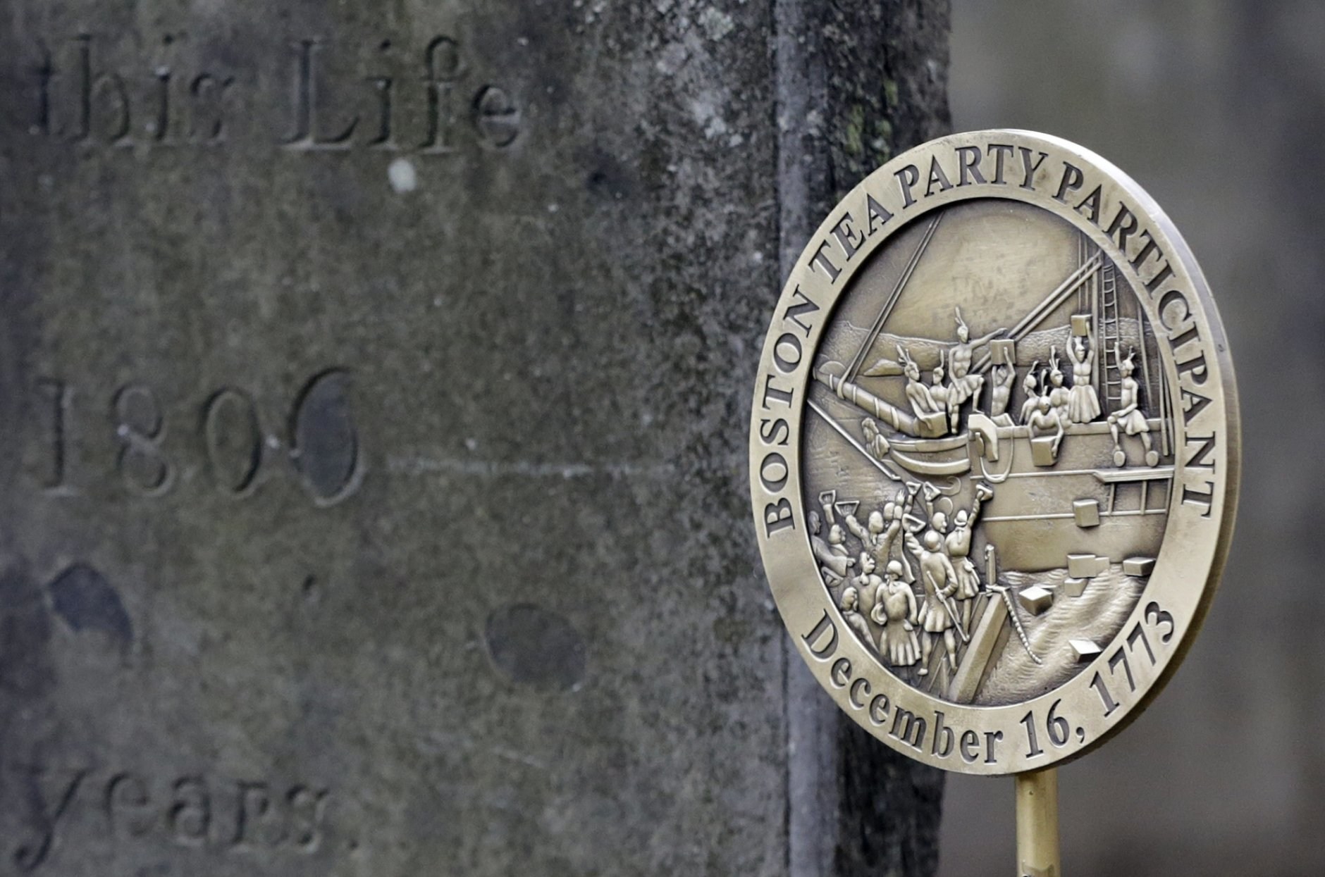 A commemorative marker stands, Tuesday, Nov. 27, 2018, at Central Burying Ground on Boston Common at the gravesite of Bartholomew Trow, a participant in the Dec. 16, 1773 protest known as the Boston Tea Party. This year is the 245th anniversary of the protest during which colonists protesting taxation without representation threw British tea into Boston Harbor, considered a pivotal event that led to the American Revolution. (AP Photo/Elise Amendola)