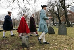 Actor-interpreters from the Boston Tea Party Ships and Museum, from left, Tim Lawton, Jillian Couillard, Sierra Grabowska and Stephen Chueka walk after placing commemorative markers, Tuesday, Nov. 27, 2018, at Central Burying Ground on Boston Common at the graves of participants in the Dec. 16, 1773 protest known as the Boston Tea Party. This year is the 245th anniversary of the protest during which colonists protesting taxation without representation threw British tea into Boston Harbor, considered a pivotal event that led to the American Revolution. (AP Photo/Elise Amendola)
