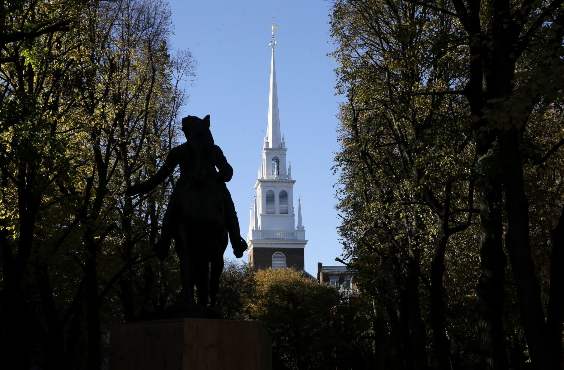 In this Wednesday, Nov. 7, 2018 photo Old North Church stands behind a statue of Paul Revere in the North End neighborhood of Boston. A bronze wreath and plaque that forms part of a memorial, which includes thousands of dog tags honoring soldiers killed in Iraq and Afghanistan, has been installed on the grounds of the church. The new plaque and wreath help explain the meaning of the dog tags and acknowledge Britain's contribution and sacrifice. (AP Photo/Steven Senne)