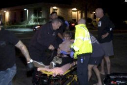 "In this image taken from video a victim is treated near the scene of a shooting, Wednesday evening, Nov. 7, 2018, in Thousand Oaks, Calif.  A hooded gunman dressed entirely in black opened fire on a crowd at a country dance bar holding a weekly ""college night"" in Southern California, killing multiple people and sending hundreds fleeing including some who used barstools to break windows and escape, authorities said Thursday. The gunman was later found dead at the scene.  (RMG News via AP)"