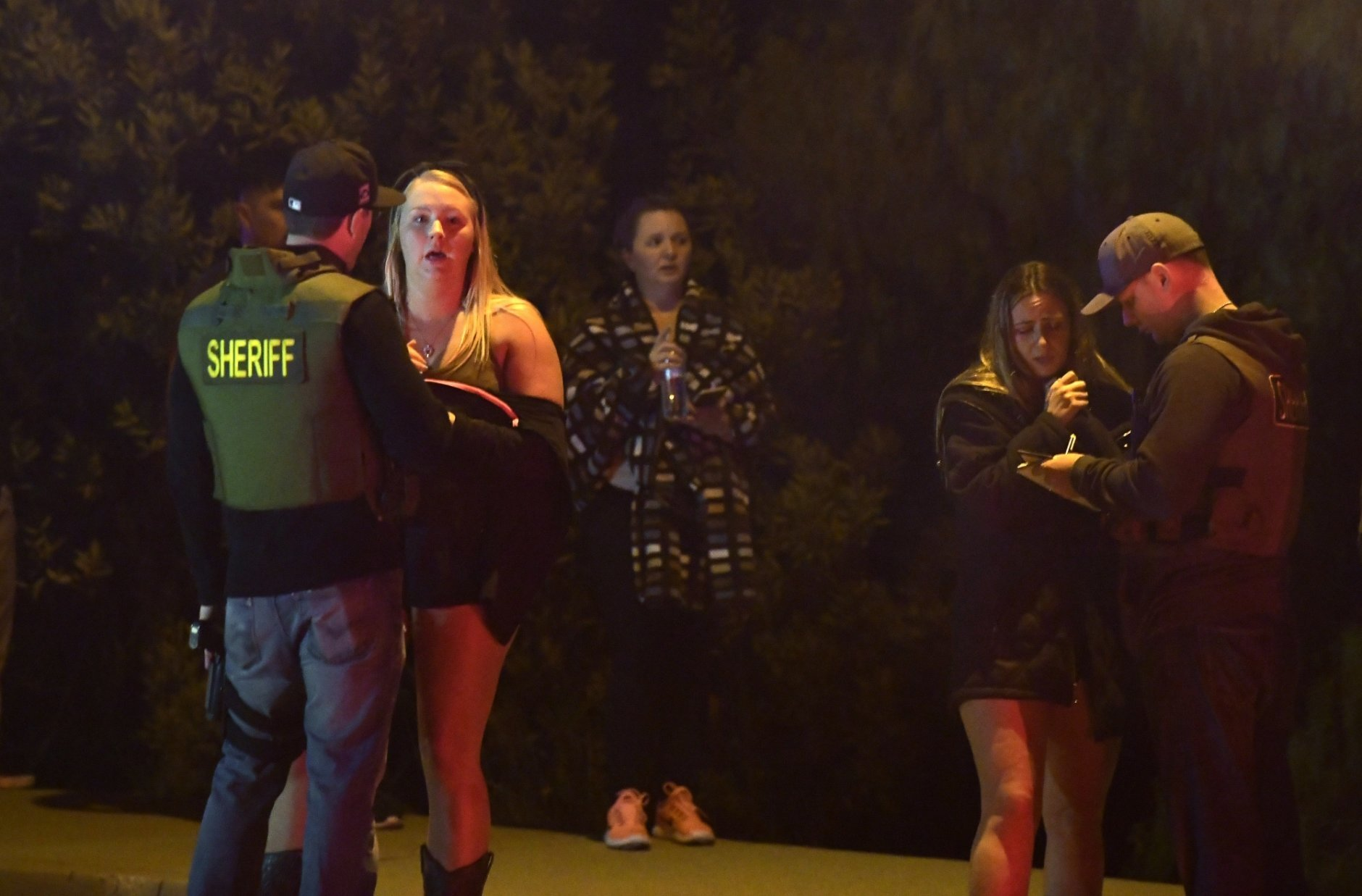 """Sheriff's deputies speak to potential witnesses as they stand near the scene of a mass shooting Thursday, Nov. 8, 2018, in Thousand Oaks, Calif., where a gunman opened fire Wednesday night inside a country dance bar crowded with hundreds of people on """"college night,"""" killing at least 12 people, including a sherif's deputy who rushed to the scene. Ventura County sheriff's spokesman says the gunman is dead inside the bar. (AP Photo/Mark J. Terrill)"""
