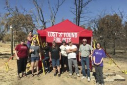 "In this undated photo, Volunteers with Carr Fire Pet Rescue and Reunification pose with their ""Lost and Found Fire Pets"" kiosk in Redding, Calif. Volunteers continue to track and catch missing pets nearly two months after the fire was extinguished. They post pictures of the rescued pets in hopes that their owners will recognize them and reunite with them. More than 80 families who lost their homes in California's deadly Carr Fire in July have learned weeks or months later that their dogs and cats had survived the deadly disaster. (Courtesy of Stacey Jimenez via AP)"