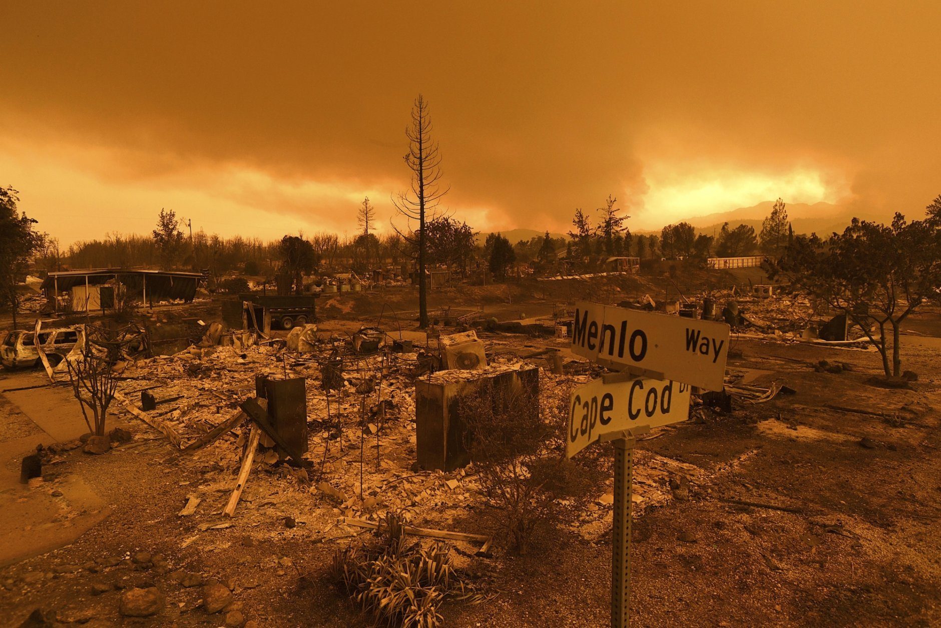 In this July 27, 2018, file photo, homes leveled by the Carr Fire line are seen in the Lake Keswick Estates area of Redding, Calif.  More than 80 families who lost their homes in California's deadly Carr Fire in July have learned weeks or months later that their dogs and cats had survived the deadly disaster. A network of about 35 volunteers, called Carr Fire Pet Rescue and Reunification, is responsible for many of the happy endings and continues to track and catch missing pets nearly two months after the fire was extinguished. (AP Photo/Noah Berger, File)
