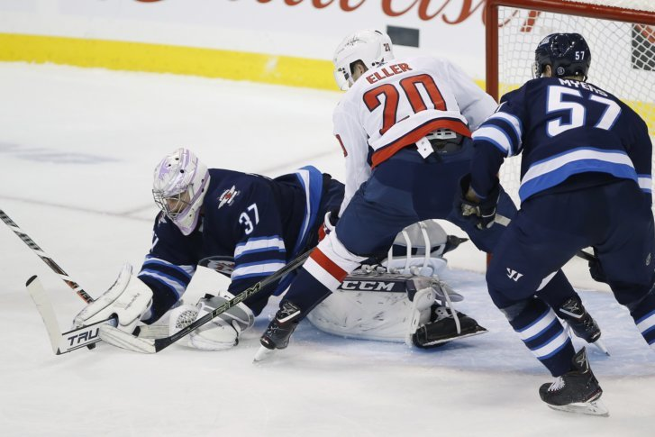 Winnipeg Jets goaltender Connor Hellebuyck (37) jumps on a loose rebound as  Washington Capitals  Lars Eller (20) moves in and Jets  Tyler Myers (57)  defends ... 272e3b78d