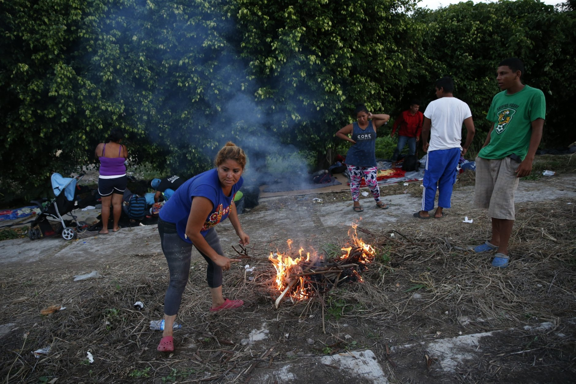 Migrants light a fire for cooking as a thousands-strong caravan of Central Americans hoping to reach the U.S. border stops for the night, in Matias Romero, Oaxaca state, Mexico, Thursday, Nov. 1, 2018. Most of the main caravan of Central American migrants spent a rain-drenched night outside, before continuing their slow walk through southern Mexico.(AP Photo/Rebecca Blackwell)