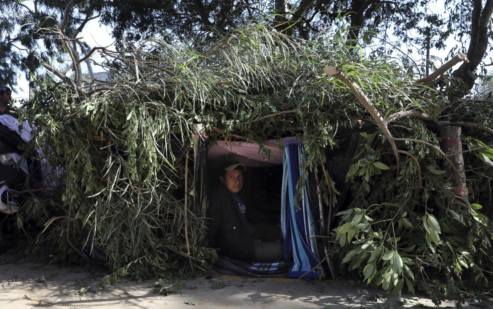 """Honduran migrant Mauro Hernandez rests inside a makeshift tent at a temporary shelter in Tijuana, Mexico, early Saturday morning, Nov. 17, 2018. Many of the nearly 3,000 migrants have reached the border with California. The mayor has called the migrants' arrival an """"avalanche"""" that the city is ill-prepared to handle. (AP Photo/Rodrigo Abd)"""