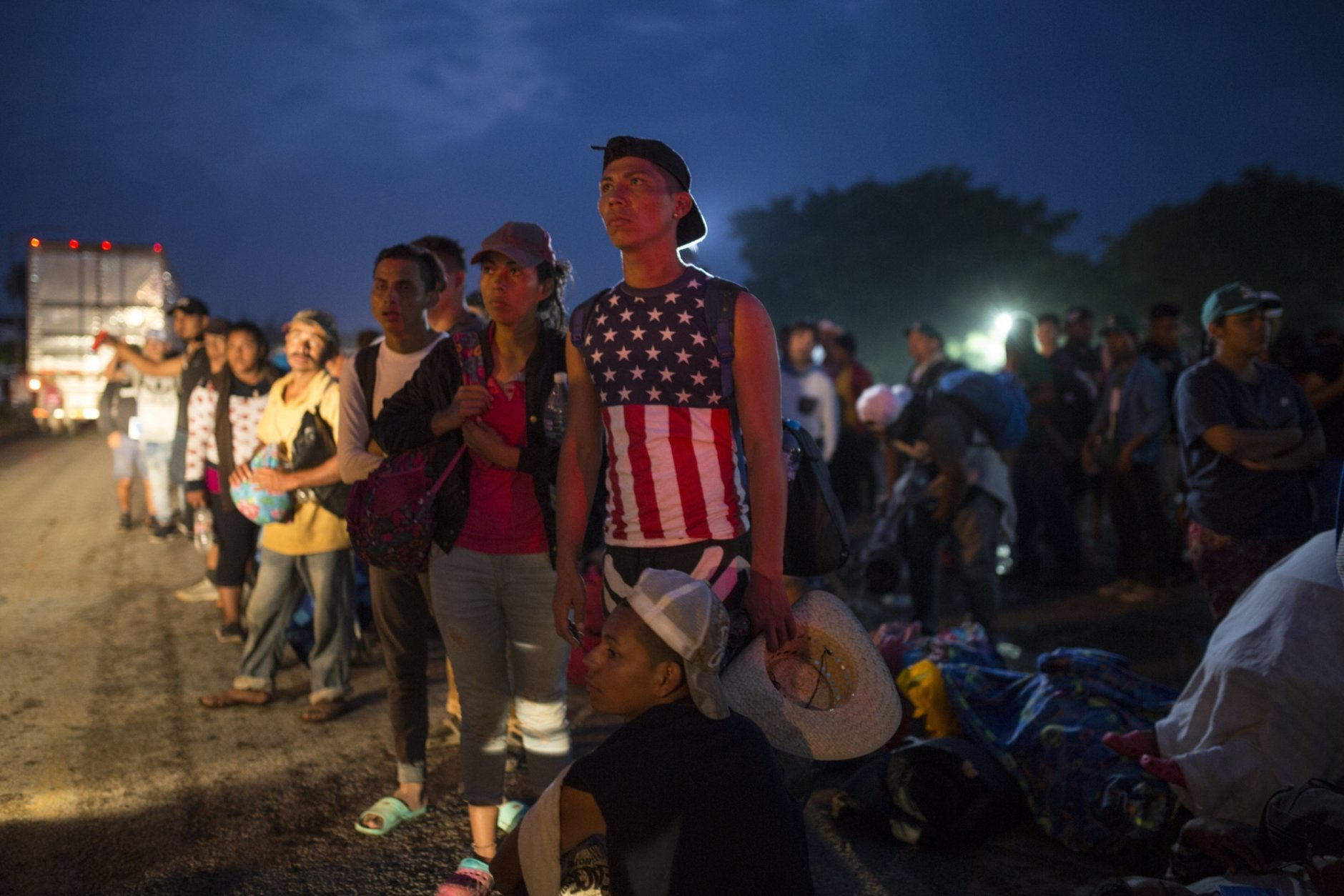 Central American migrants, part of the caravan hoping to reach the U.S. border, wait for a ride in Donaji, Oaxaca state, Mexico, Friday, Nov. 2, 2018. The migrants had already made a grueling 40-mile (65-kilometer) trek from Juchitan, Oaxaca, on Thursday, after they failed to get the bus transportation they had hoped for. But hitching rides allowed them to get to Donaji early, and some headed on to a town even further north, Sayula. (AP Photo/Rodrigo Abd)