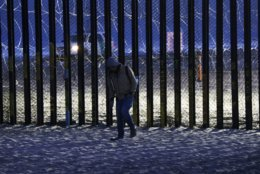 """A resident walks near barriers, wrapped in concertina wire, separating Mexico and the United States, where the border meets the Pacific Ocean, in Tijuana, Mexico, Saturday, Nov. 17, 2018. Many of the nearly 3,000 migrants have reached the border with California. The mayor has called the migrants' arrival an """"avalanche"""" that the city is ill-prepared to handle. (AP Photo/Marco Ugarte)"""