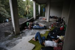 Migrants sleep inside a hotel that was abandoned after being damaged in last year's earthquake, in Matias Romero, Oaxaca state, Mexico, Thursday, Nov. 1, 2018. Most of the main caravan of Central American migrants spent a rain-drenched night outside, before continuing their slow walk through southern Mexico.(AP Photo/Rebecca Blackwell)