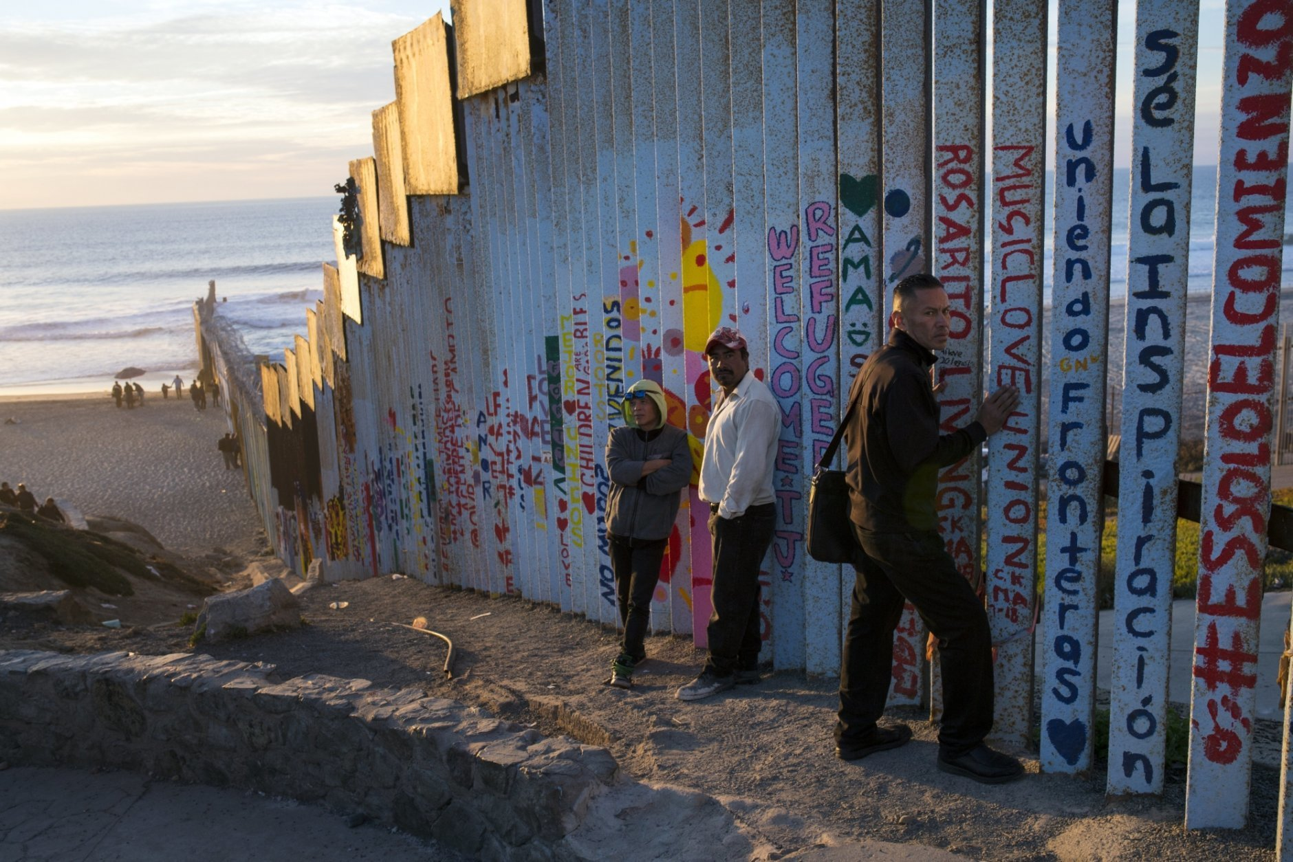 People hang out at the Mexican side of the border structure that separates Mexico from the U.S., at the Pacific Ocean, Tijuana, Mexico, Friday, Nov. 16, 2018. As thousands of migrants in a caravan of Central American asylum-seekers converge on the doorstep of the United States, what they won't find are armed American soldiers standing guard. (AP Photo/Rodrigo Abd)
