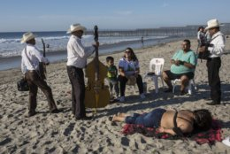 Musicians talk to tourists after performing at the Mexican side of the border with the U.S. at the Pacific Ocean, Tijuana, Mexico, Friday, Nov. 16, 2018. With about 3,000 Central American migrants having reached the Mexican border across from California and thousands more anticipated, the mayor of Tijuana said Friday that the city was preparing for an influx that will last at least six months and may have no end in sight.  (AP Photo/Rodrigo Abd)