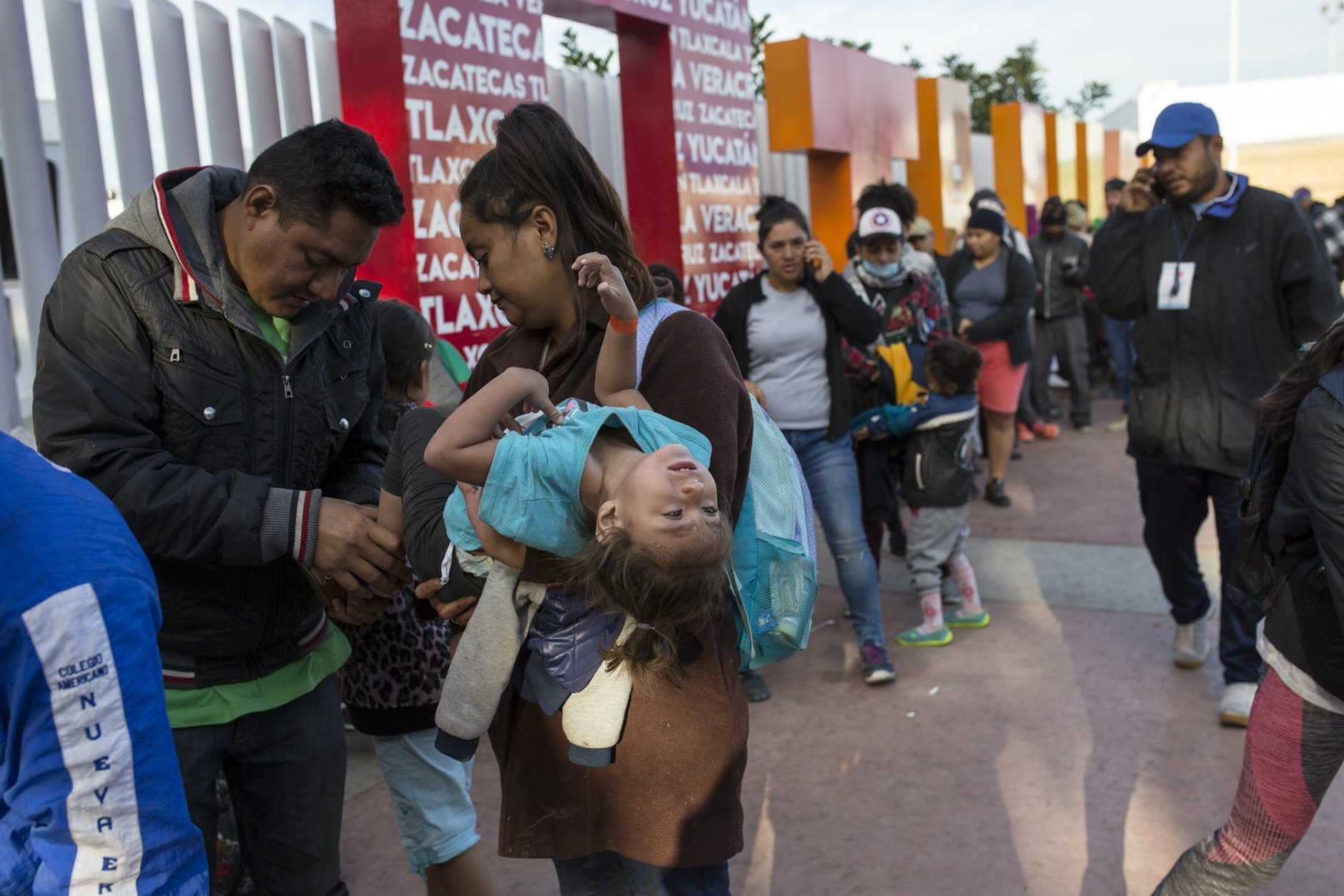 Sairy Hueso, part of the Central American migrant caravan, carries her daughter Etzabe Ponce, as she stands next to her husband while waiting in line to receive a number as part of the process to apply for asylum in the United States, at the border in Tijuana, Mexico Tijuana, Mexico, Friday, Nov. 16, 2018. As thousands of migrants of asylum-seekers converge on the doorstep of the United States, what they won't find are armed American soldiers standing guard, that's because U.S. military troops are prohibited from carrying out law enforcement duties. (AP Photo/Rodrigo Abd)