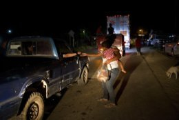 Honduran migrant Luz  Padilla Valverde, carrying her child, gets a contribution from a passing driver in Matias Romero, Oaxaca state, Mexico, Thursday, Nov. 1, 2018. Most of the main caravan of Central American migrants spent a rain-drenched night outside, before continuing their slow walk through southern Mexico.(AP Photo/Rebecca Blackwell)