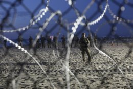 U.S. Border Patrol agents are seen though the border structure from the Mexican side at the Pacific Ocean, Tijuana, Mexico, Friday, Nov. 16, 2018. As thousands of migrants in a caravan of Central American asylum-seekers converge on the doorstep of the United States, what they won't find are armed American soldiers standing guard. (AP Photo/Rodrigo Abd)