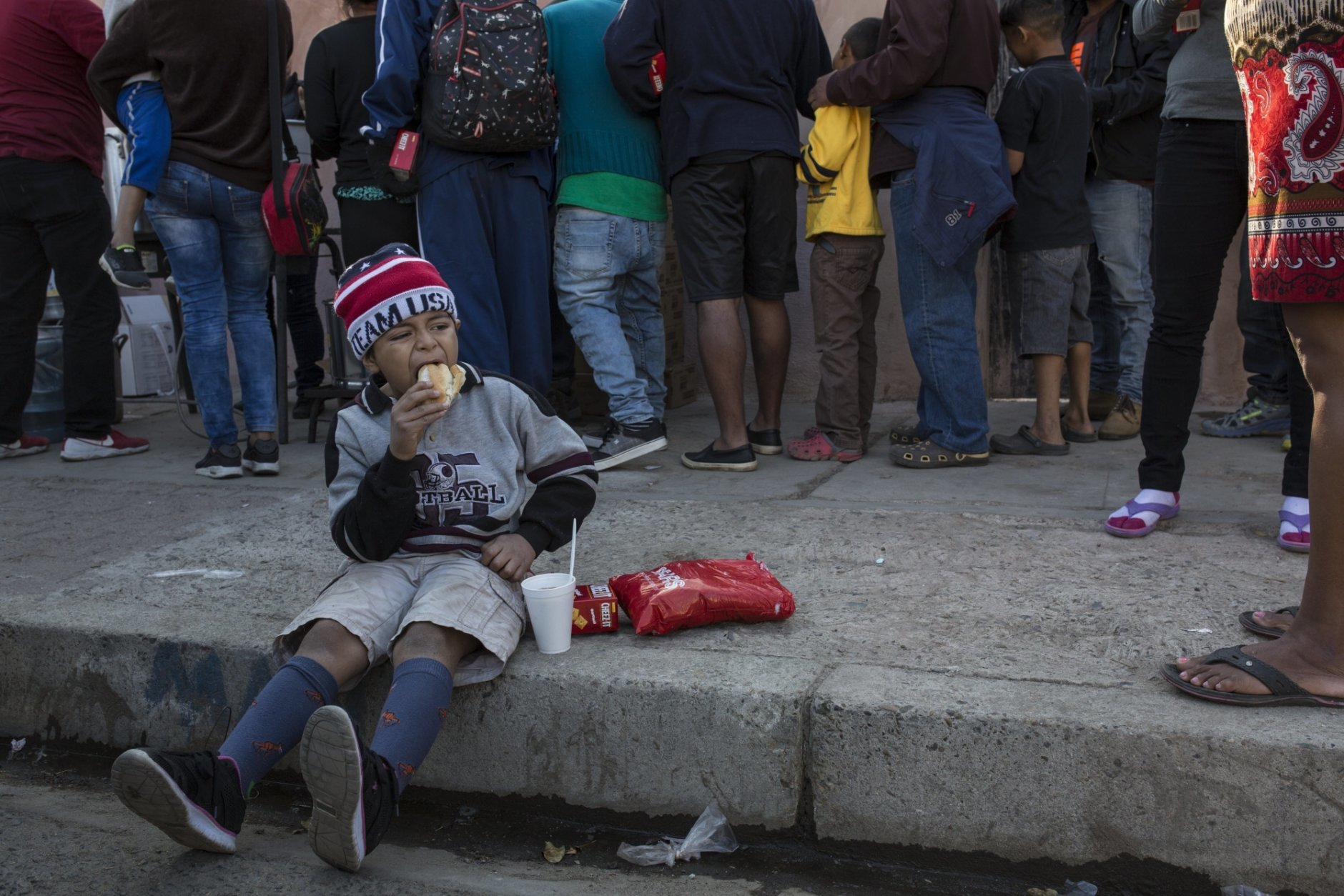 """A Central American migrant boy eats a donated breakfast at a temporary shelter in Tijuana, Mexico, early Saturday morning, Nov. 17, 2018. Many of the nearly 3,000 migrants have reached the border with California. The mayor has called the migrants' arrival an """"avalanche"""" that the city is ill-prepared to handle. (AP Photo/Rodrigo Abd)"""