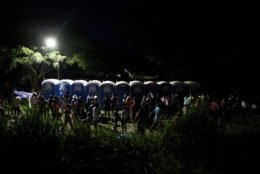 Migrants wait in lines to use portable toilets at a makeshift campground where a thousands-strong caravan of Central Americans hoping to reach the U.S. border stops for the night, in Matias Romero, Oaxaca state, Mexico, Thursday, Nov. 1, 2018. Most of the main caravan of Central American migrants spent a rain-drenched night outside, before continuing their slow walk through southern Mexico.(AP Photo/Rebecca Blackwell)