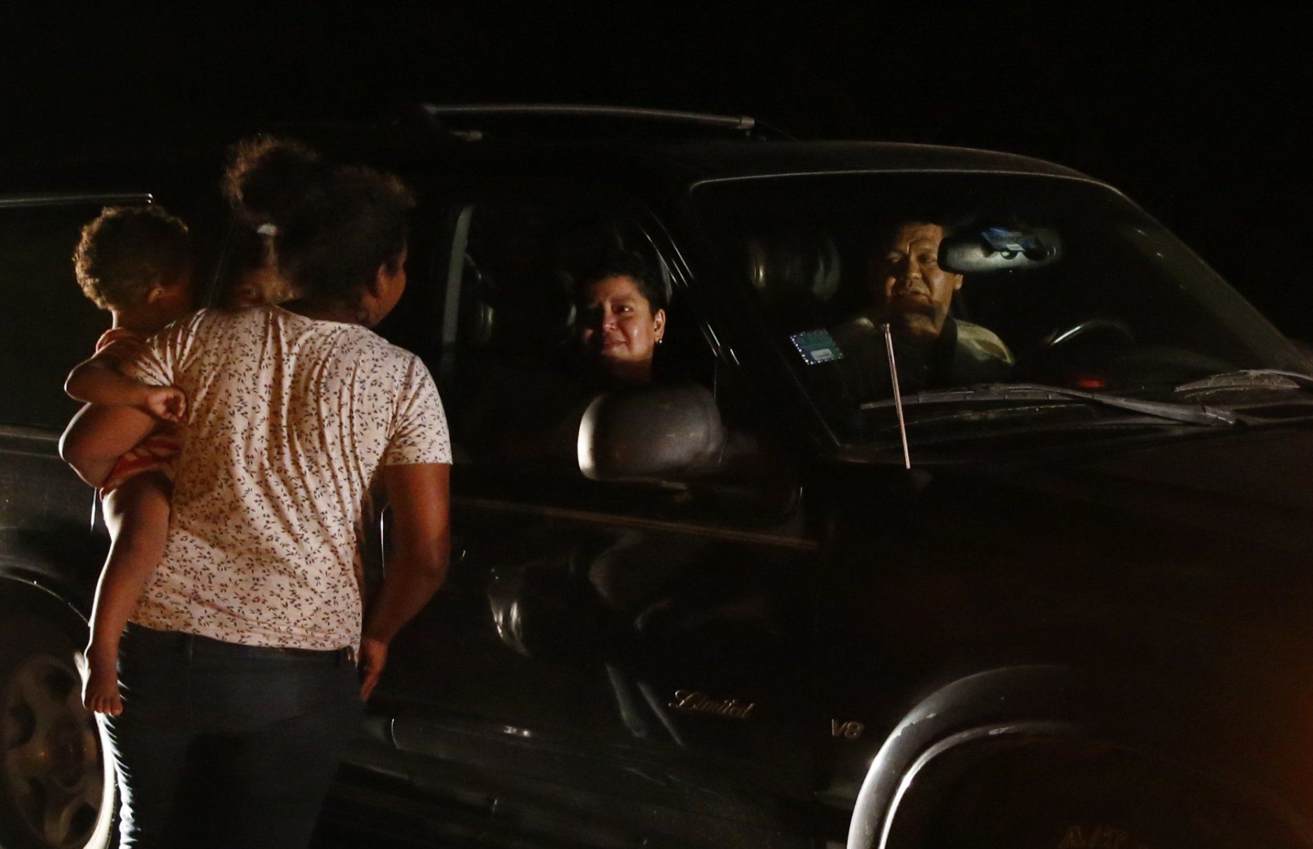 Mexicans in a car stop to talk to Honduran migrant Luz  Padilla Valverde, carrying her child, as she begs for contributions of one peso (5 cents), in Matias Romero, Oaxaca state, Mexico, Thursday, Nov. 1, 2018. Most of the main caravan of Central American migrants spent a rain-drenched night outside, before continuing their slow walk through southern Mexico.(AP Photo/Rebecca Blackwell)