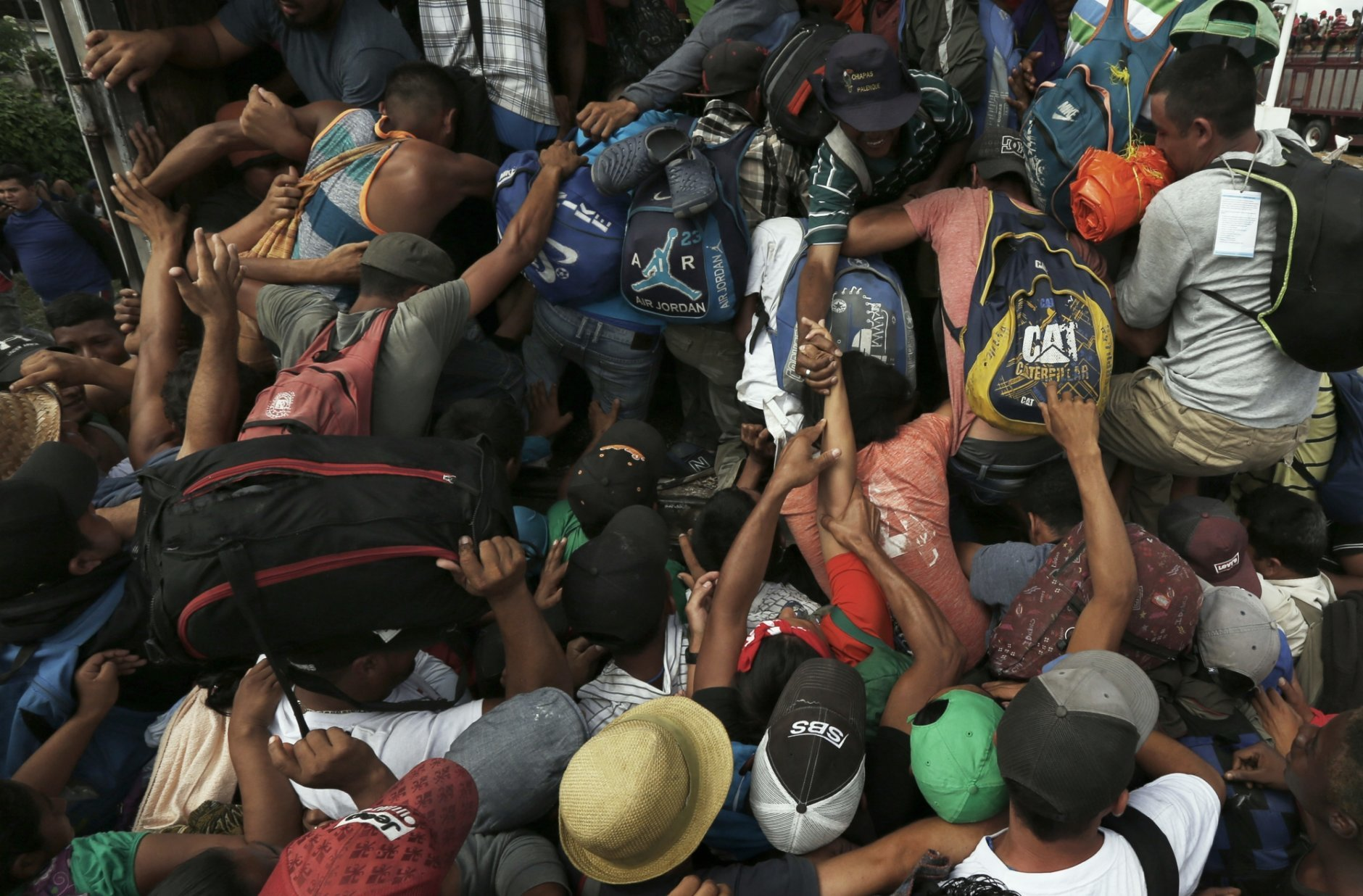 Central American migrants, part of the caravan hoping to reach the U.S. border, scramble to get a ride on a truck, in Isla, Veracruz state, Mexico, Saturday, Nov. 3, 2018. The 150 buses that the Governor of Veracruz promised to the Central American migrants to get to Mexico City, did not arrive. (AP Photo/Marco Ugarte)