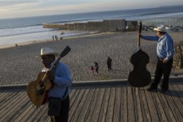 """Musicians called """"Talismanes de Tijuana"""" wait for customers near the border structure between Mexico and the U.S. at the Pacific Ocean, Tijuana, Mexico, Friday, Nov. 16, 2018. As thousands of migrants in a caravan of Central American asylum-seekers converge on the doorstep of the United States, what they won't find are armed American soldiers standing guard. (AP Photo/Rodrigo Abd)"""