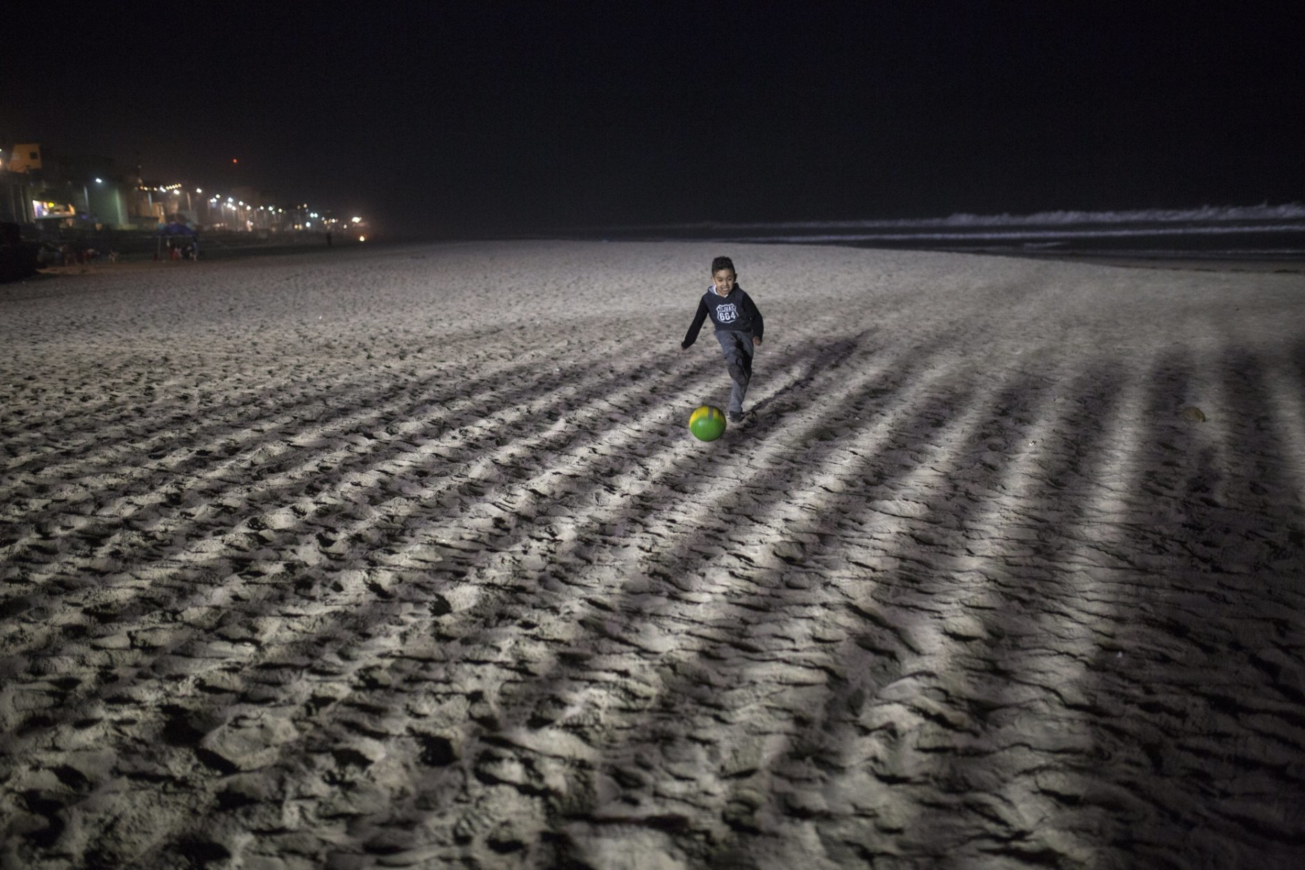 A boy plays soccer at the Mexican side of the border with the U.S. at the Pacific Ocean, Tijuana, Mexico, Friday, Nov. 16, 2018. With about 3,000 Central American migrants having reached the Mexican border across from California and thousands more anticipated, the mayor of Tijuana said Friday that the city was preparing for an influx that will last at least six months and may have no end in sight. (AP Photo/Rodrigo Abd)