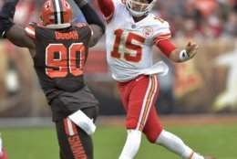 Kansas City Chiefs quarterback Patrick Mahomes (15) passes the ball over Cleveland Browns defensive end Emmanuel Ogbah (90) during the second half of an NFL football game, Sunday, Nov. 4, 2018, in Cleveland. (AP Photo/David Richard)